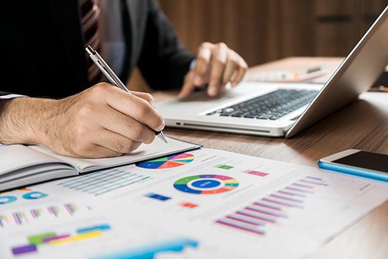 Mann mit Laptop und Heft am Schreibtisch macht sich Notizen zu Diagrammen