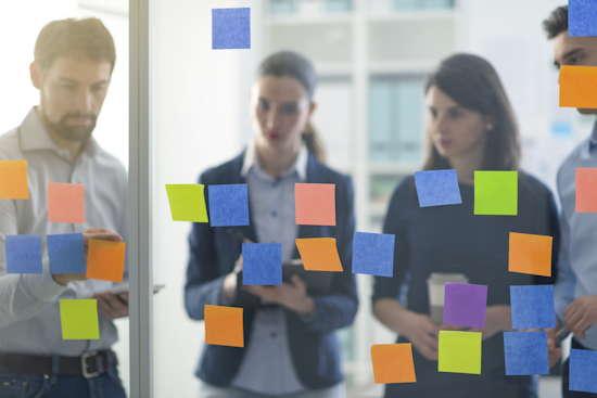 Team durch eine Glaswand fotografiert, auf der bunte Zettel kleben.