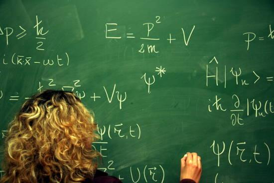 Grüne Tafel (von der Schreibenden ist nur der Kopf von hinten und die Hand zu sehen) beschrieben mit diversen Formeln