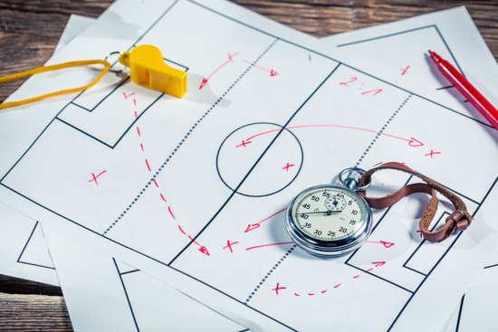 Fusball-Taktikschema, darauf liegend Pfeife und Stoppuhr
