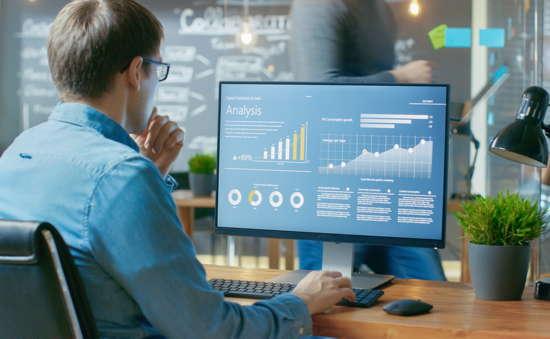 Junger Mann mit Brille schaut sich Statistiken auf einem Computerbildschirm an.