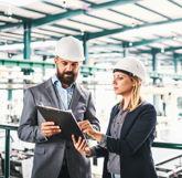 Wirtschaftsingenieure in Anzügen in einer Fabrikhalle