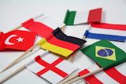 Kleine Flaggen verschiedener Länder (u.a. Deutschland, Türkei, Brasilien, Italien) auf Zahnstochern liegen auf weißem Hintergrund