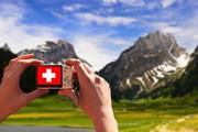 Alpenpanorama, ins Bild gehalten wird eine Kamera, auf der statt dem Panorama die Fahne der Schweiz angezeigt wird