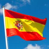 Flagge von Spanien an einem Fahnenmast vor blauem Himmel