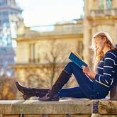 Eine Studentin sitze auf einer Mauer und liest. Im Hintergrund: der Eifelturm