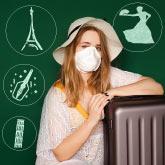 Studentin mit Koffer und Maske sitzt vor einer Tafel mit Skizzen von Sehenswürdigkeiten verschiedener Länder