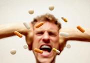Pillen kreisen vor dem Gesicht eines Menschen, der sich die Ohren zuhält und den Mund aufreißt