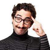 Mann mit exzentrischem Bart und Gesichtsausdruck tippt sich an die Stirn – er hat eine Idee