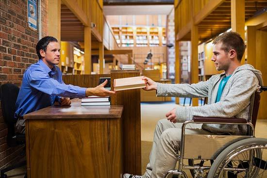 Student im Rollstuhl an der Bücherrückgabe der Bibliothek