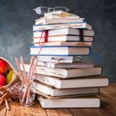 Stapel Bücher mit Markierungen, dazu einige Äpfel und Bleistifte