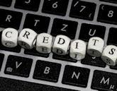 """Computer-Tastatur, auf der aus Buchstaben-Holzblöcken """"Credits"""" steht"""