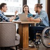 Drei Studierende, davon einer mit Rollstuhl, sitzen zusammen