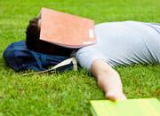 Student liegt auf Wiese, Heft über dem Kopf
