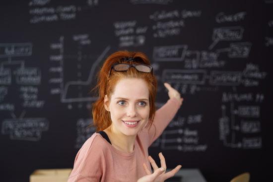 Frau steht vor Tafel und hält einen Vortrag