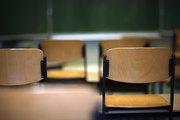 Leere Stühle in einem Seminarraum, im Hintergrund leere Tafel erkennbar