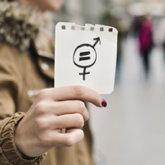 Frau hält ein Notizzettel mit den Geschlechtersymbolen und einem Gleichheitszeichen ins Bild