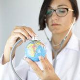 Ärztin untersucht Mini-Globus mit Stethoskop