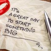 """Tasse Kaffe, Kugelschreiber und Serviette, auf der """"It's a great day to start something BIG"""" geschrieben wurde"""