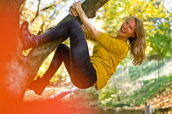 Junge Frau klettert auf einem Baum herum