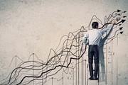 Mann auf Leiter vor Wand mit (Börsen-)Kurven