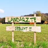 """Wiese mit Kühen, davor großes Schild mit Aufschrift """"Landärzte gesucht"""""""