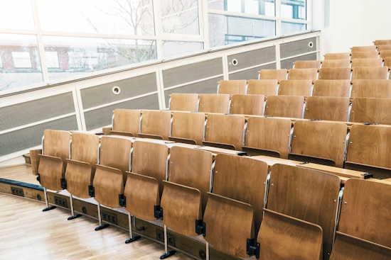 Leerer Hörsaal mit hochgeklappten Sitzen.
