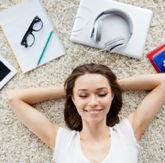 Frau liegt mit geschlossenen Augen auf dem Rücken, um ihren Kopf liegen Tablet, Bücher, Notizblöcke, Brille, Stifte und Kopfhörer
