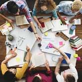Eine Gruppe von Studierenden sitzt am Tisch und lernt