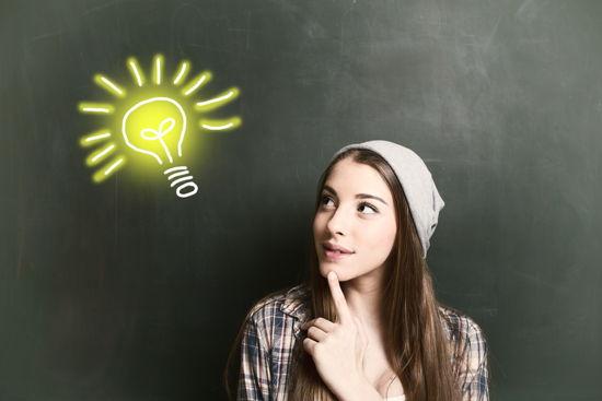 """Studentin vor Tafel, auf der eine leuchtende Glühbirne aufgemalt ist (""""Ein Licht geht auf"""")"""