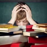 Ein deprimierter Student sitzt hinter einem Berg von Büchern