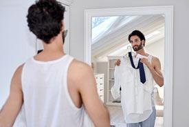 Ein Mann hält sich am Spiegel ein Hemd und eine Krawatte an - er macht sich für die Arbeit fertig