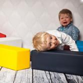 """Kinder spielen mit """"Modulen"""", ein Kind sitzt unglücklich im Hintergrund"""