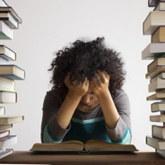 Studentin sitzt nachdenklich vor einem Buch, zwischen Bücherstapeln