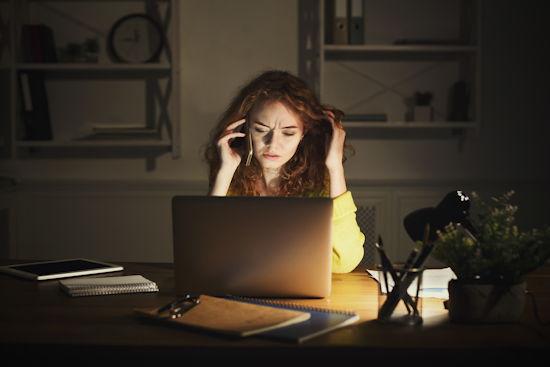Studentin sitzt vor ihrem Laptop und telefoniert mit ihrem Smartphone, offenbar nachts
