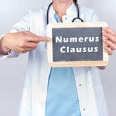 """Ärztin hält Tafel mit Aufschrift """"Numerus Clausus"""""""