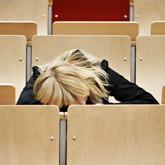 Studentin im Hörsaal, offenbar schlafend.