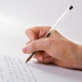 Eine Hand, die gerade einen Kugelschreiber hält und einen Text schreibt