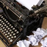 Altertümliche Schreibmaschine mit eingespanntem Blatt Papier und zerknülltem Papier daneben