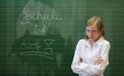 Genervte Schülerin steht vor einer Tafel, auf der Schule ist doof steht