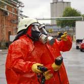 Zwei Menschen in Schutzausrüstung mit Helm, Handschuhen und Atemmaske