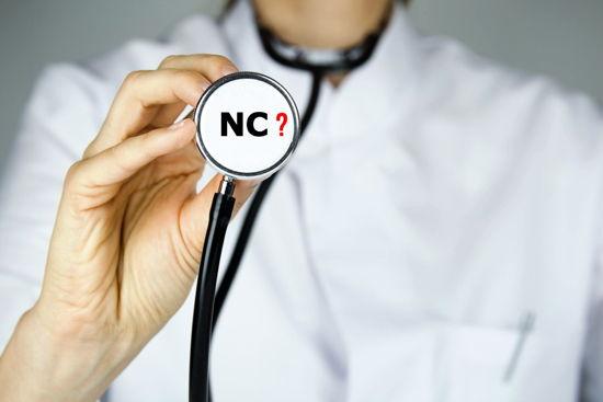"""Ärztin hält Stethoskop in die Kamera, darauf Aufschrift """"NC?"""""""