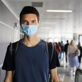 Junger Mann mit Maske steht auf Laufband im Flughafen.