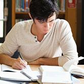 Student sitzt in der Bibliothek an einer Hausarbeit