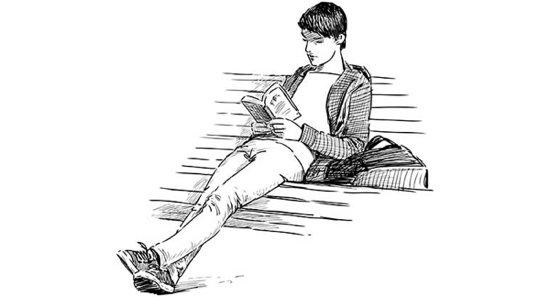 Ein Student sitzt lesend auf einer Bank