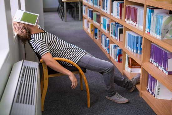 Student sitzt in einer Bibliothek und hat ein Buch auf dem Gesicht liegen –er schläft.