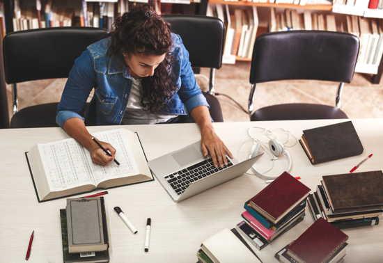Studentin sitzt mit Laptop und Büchern an einem Tisch in einer Unibliothek