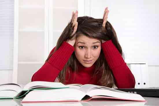 Studentin sitzt verzweifelt über einem Buch