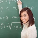 Studentin schreibt Formel an eine Tafel