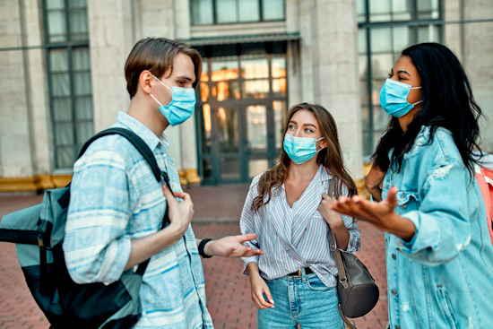 Drei Studierende mit Alltags-Maske unterhalten sich gestikulierend vor Hochschulgebäude